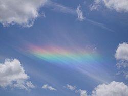 A circumhorizontal arc projected onto a sheet of striated cirrus clouds seen through a hole in lower-level cumulus clouds.