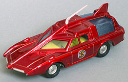The photograph depicts a scale toy replica of an unarmoured, futuristic car that is deep red in colour and incorporates an angular bonnet and roof.