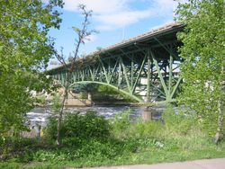 picture of the bridge painted green and surrounded by green foliage seen from the Mississppi bank