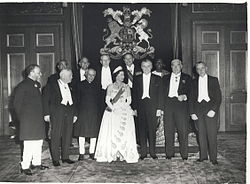 A number of older men in formal dress surround a young woman with a white gown.