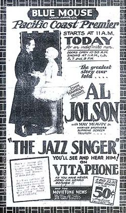 "Advertisement from the Blue Mouse Theater announcing the Pacific Coast premiere of The Jazz Singer, billed as ""The greatest story ever told"". A photo of stars Al Jolson and May McAvoy accompanies extensive promotional text, including the catchphrase ""You'll see and hear him on Vitaphone as you've never seen or heard before"". At the bottom is an announcement of an accompanying newsreel."