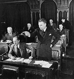 Diefenbaker, standing in a legislative chamber, dramatically points in front of him. His hair is greying, and he appears much the way he will as Prime Minister.