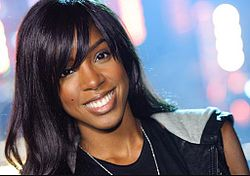 A dark-skinned woman with black hair, wearing a white top and blue jeans, is holding a microphone.