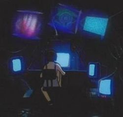 A young girl in a white shift sits with her back to us in the dark, focusing her attention on many glowing computer screens which surround her.