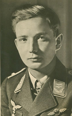 The head and shoulders of a young man, shown in semi-profile. He wears a military uniform with an Iron Cross displayed at the front of his shirt collar. His hair is dark and short and combed to his right, his nose is long and straight, and his facial expression is emotionless; looking into the camera.