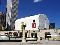 A large white tent sits on the roof of a cafe building set in front of a skyscraper and blue sky.