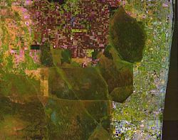 A color satellite image of the northern Everglades showing green chunks of Everglades surrounded by white settlement areas of the South Florida Metropolitan Area to the east and red agricultural fields in the Everglades Agricultural Area to the north