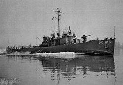 The USS PC-815, a single-masted vessel running at speed with a large wake, and with a deck gun prominent on the bow