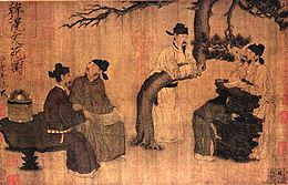 Four men dressed in robes and black square cut hats gather around a tree talking to one another. Three are sitting on rocks while the fourth is leaning over a horizontally bent branch of the tree.
