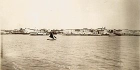 Photograph looking across water with a small sail boat in the foreground and buildings along the shore in the background
