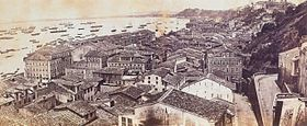 Photograph looking down a hillside overlooking the buildings of a town with a harbor beyond which is crowded with various vessels
