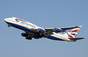 A British Airways 747-400 in white, blue and red livery during takeoff with its landing gear retracting.
