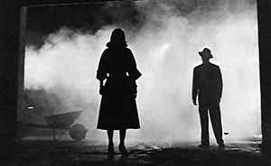 A high-contrast black-and-white image. White fog or smoke fills the background. In the left foreground is the silhouette of a woman wearing a calf-length skirt. To the right, at a further distance, is the silhouette of a man wearing a fedora.