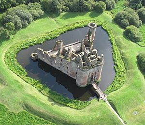 An aerial view of a stone building with a triangular plan. It is surrounded by a ditch filled with water.