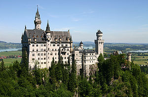 A castle of fairy-tale appearance sitting high on a ridge above a wooded landscape. The walls are of pale stone, the roofs are of steep pitch and there are a number of small towers and turrets.