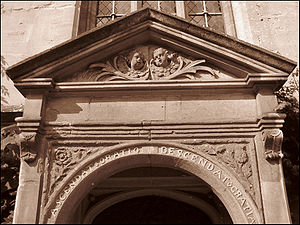 """Part of a stone doorway.  The top is triangular, with the heads of two cherubs in the panel beneath. On the curved arch immediately above the entrance, the words """"Ascendat oratio descendat Gratia""""; a rose and a thistle on the adjoining panels"""