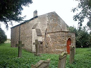 A small, very plain stone church seen from an angle, consisting of a single cell with a porch at the west end, a bellcote at the far end, and no visible windows