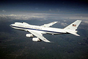 White jet with blue cheatline in-flight over land, flying left. The aircraft features a distinctive bump above the usual 747's trademark nose profile
