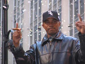 A dark-skinned man in a black baseball cap and black leather jacket holding up both his hands with his index fingers extended. He is holding a cigar in his right hand.
