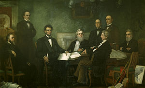 A dark-haired, bearded, middle-aged man holding documents is seated among seven other men.