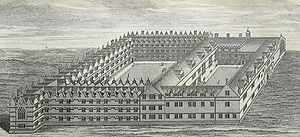 A bird's-eye view of two joined quadrangles of buildings, the left quadrangle being slightly larger than the right; the buildings on the far left extend beyond the adjoining range slightly, terminating in a large Gothic window; regularly positioned smaller windows and gables throughout both quadrangles