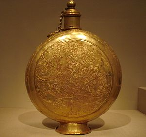 A circular, bulbous-disc-shaped golden canteen engraved with designs of a dragon and clouds, with a built-on stand and a cylindrical top that has a chain-link handle