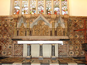 A marble reredos beneath a stained glass window, with three scenes from the Crucifixion; a granite altar with six pillars