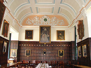 A wood-panelled hall, with a large portrait of Elizabeth I in the middle of the far wall; other portraits alongside and around the walls; a white plaster ceiling with light blue decoration