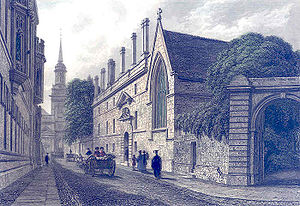 A three-storey building with regularly positioned windows, chimneys and an elaborated decorated entrance, adjoining a building with a large Gothic window, with a street in front on which there are people walking, and horses and carriages. There is a church spire in the distance.
