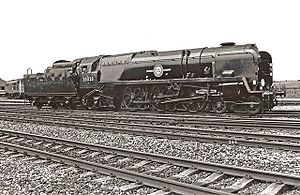 A posed side-and-front view of the rebuilt form of the locomotive, standing in the sidings of a locomotive depot. The locomotive is of conventional appearance, with a visible boiler and no flat covering plates. Smoke deflectors are fitted at the front of the locomotive.