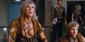 Two men are in the foreground, sitting and looking to the right. The man on the left has long, gray hair, is wearing a torn golden shirt, and his exposed chest has a large scar. The man on the right is seen from the shoulders up and has similar hair and clothes. In the background a man and woman are next to electronic controls.