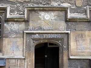 """A stone archway, without a door; above, the Roman numerals """"VI"""" in a white circle and, in chalk, two crossed rowing oars with green blades and the words """"Blades"""", """"2001"""", """"Men's 1st Torpid""""; to the left, """"Balliol SEH Keble Merton""""; to the right, a standing dragon holding a flag above the initials """"JCBC"""""""