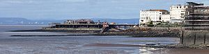 Structure supported on metal legs coming out of the sea, stretching from the land showing several white buildings to an island with buildings on it. A lifeboat house with slipway is attached to the side. In the distance across the water are hills and buildings.
