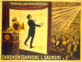 "Illustration of a theater from the rear right of the stage. At the front of the stage a screen hangs down with the projected image of a tuxedoed man holding up a text and performing. In the foreground is a gramophone with two horns. In the background, a large audience is seated at orchestra level and on several balconies. The words ""Chronomégaphone"" and ""Gaumont"" appear at both the bottom of the illustration and, in reverse, at the top of the projection screen."