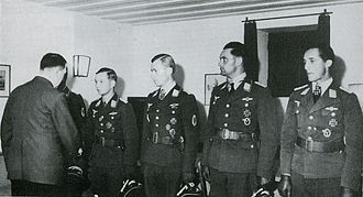 Five men all wearing military uniforms and decorations standing in row. The man on the far left is shaking hands with another man whose back is facing the camera.