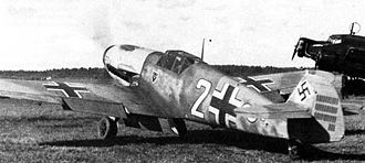 """A black and white photograph a propeller driven fighter aircraft viewed from the rear-left. The aircraft is on a grass field, engine appears to be running. It bears three black and white crosses, two on the upper wings and one on the left side of the fuselage besides a large number """"2"""". The tail rudder shows a black swastika plus rudder bears approximately 33small vertical black lines arranged in three groups of varying length."""