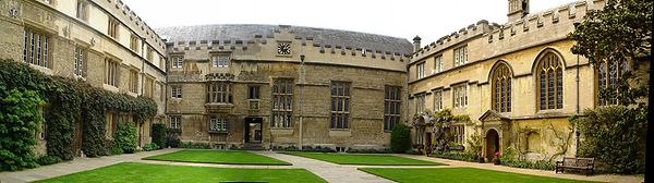 Adjoining buildings (all with battlements) on three sides of an area of grass in the middle of a quadrangle crossed by pathways from side to side and front to back; at the far side, a large building with a clock at roof level and three large windows; on the left, regularly placed windows in a three-storey building; on the right, a chapel with three arched windows alongside a three-storey house